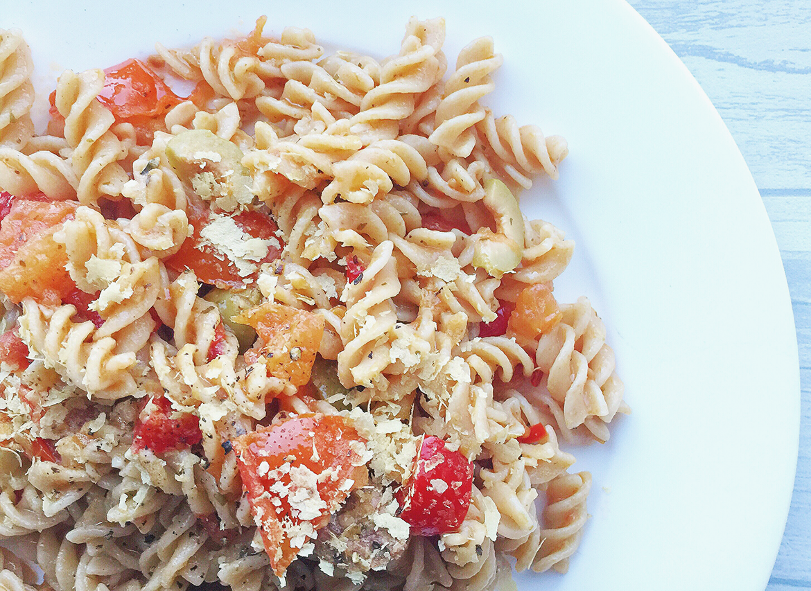 olive and tomato pasta sprinkled with nutritional yeast